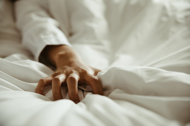 Gros plan de la femme tirant des draps blancs en extase, sentiment et concept d'émotion