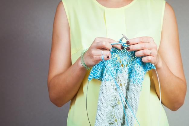 Gros plan d'une femme à tricoter