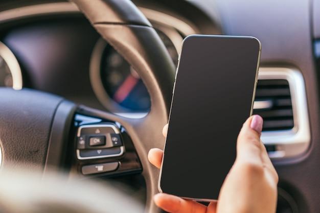 Gros plan d'une femme utilisant un smartphone en conduisant une voiture