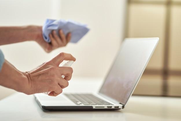 Gros plan d'une femme utilisant un spray désinfectant antibactérien et un chiffon tout en désinfectant un ordinateur portable