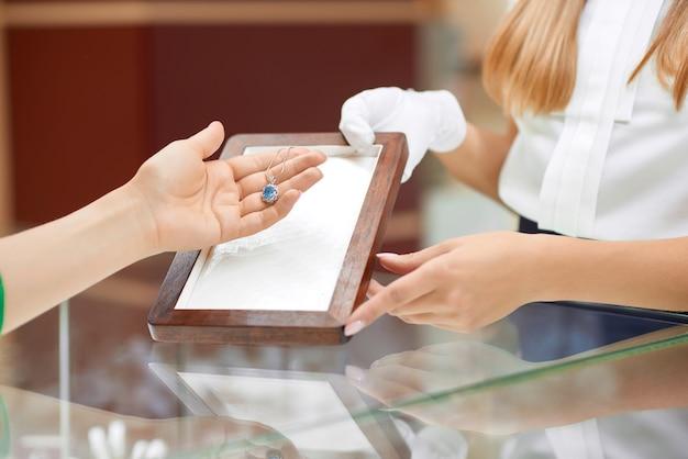 Gros plan d'une femme vérifiant un collier à la bijouterie