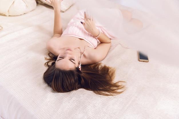 Gros plan d'une femme vêtue d'une robe rose avec un casque d'écoute de la musique