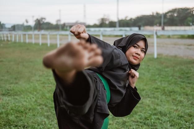 Gros plan d'une femme voilée asiatique portant un uniforme de pencak silat avec mouvement de pas