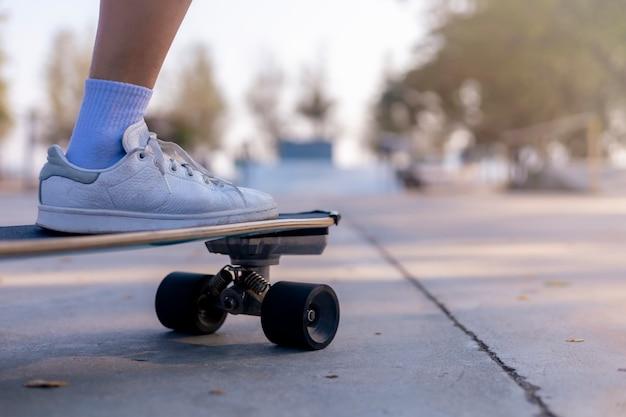Gros plan femmes asiatiques surf skate ou skateboard à l'extérieur