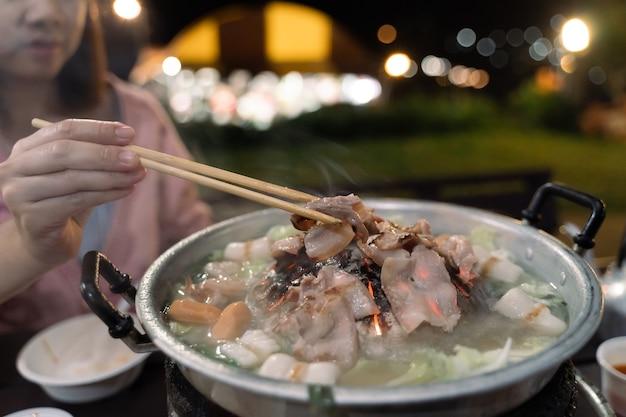 Gros plan des femmes mangeant du porc barbecue sur fond de bokeh