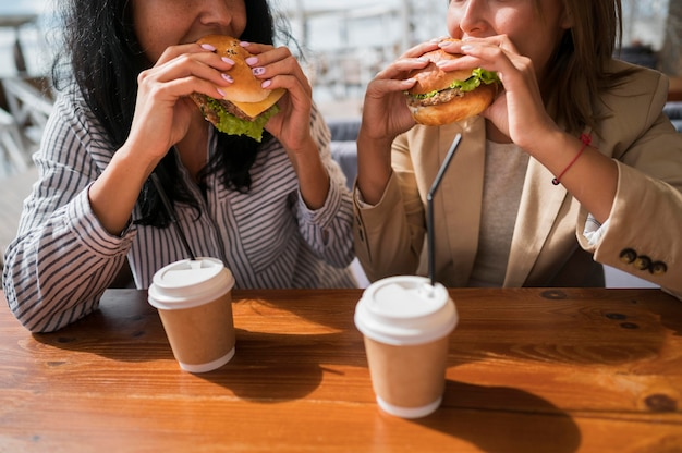 Gros plan, femmes, manger, hamburgers