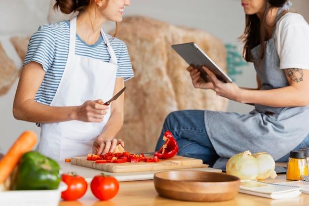 Gros plan des femmes avec tablette dans la cuisine