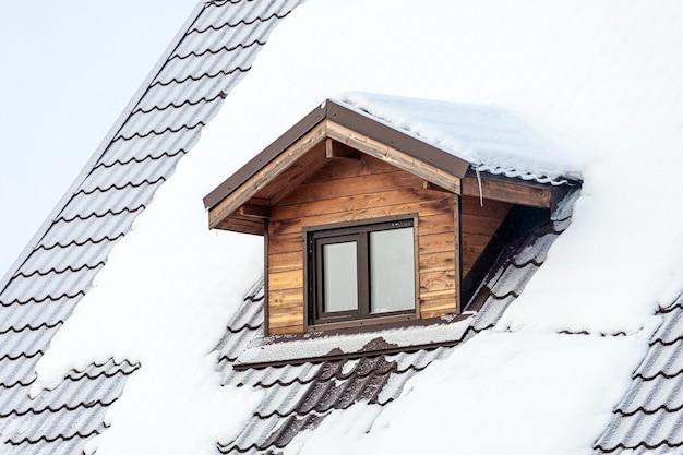 Gros plan d'une fenêtre en plastique mansardée sur une maison de campagne, le toit est recouvert de neige