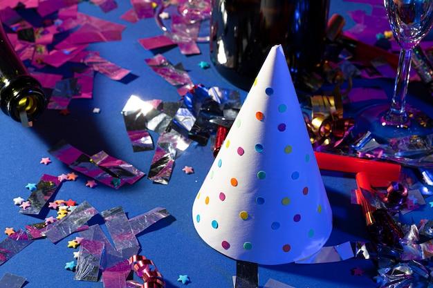 Gros plan d'une fête avec bouteille de champagne, chapeau de fête et verre