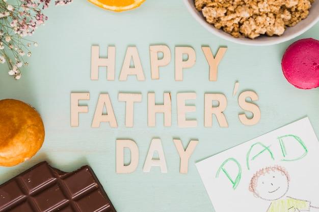 Gros plan de la fête des pères écrit au milieu de la nourriture et des dessins