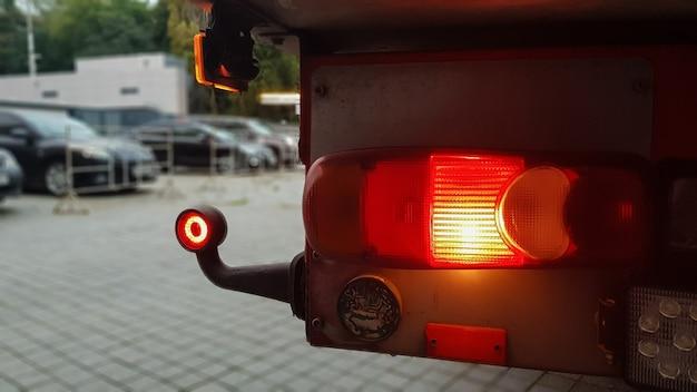 Gros plan sur le feu de position rouge rond arrière d'un camion. feu arrière pour camion. l'arrière-plan est flou. le concept de voyager en toute sécurité sur la route la nuit.