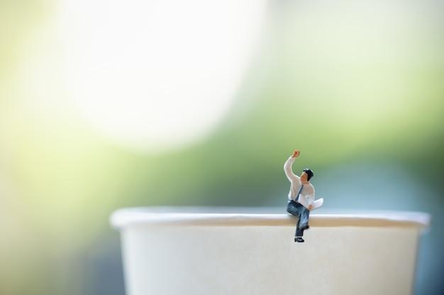 Gros plan de la figure miniature de l'homme d'affaires assis et lisez un journal sur emporter une tasse en papier avec espace de copie.