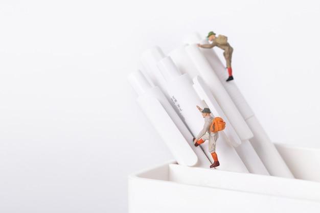 Gros plan de figurines d'étudiants grimpant sur des stylos dans un pot