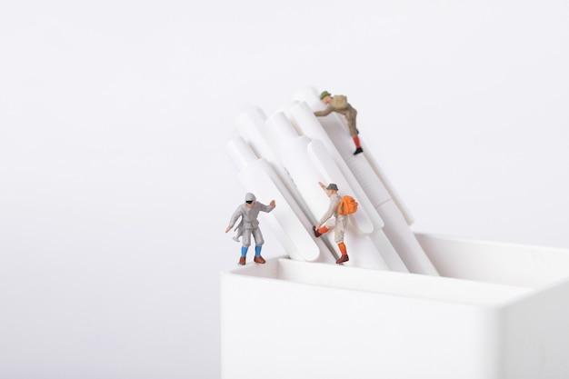 Gros plan sur des figurines d'étudiants grimpant sur des stylos dans un pot
