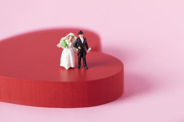 Gros plan sur des figurines de jeunes mariés sur un grand coeur rouge