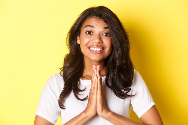 Gros plan sur une fille afro-américaine joyeuse, souriante et disant merci, appuyez les mains sur la poitrine dans un geste de prière, debout sur fond jaune