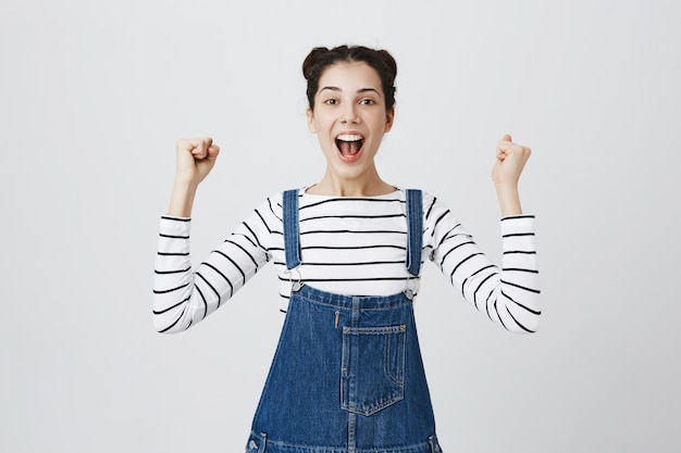 Gros plan d'une fille amusée et joyeuse triomphant, se réjouissant de la victoire, célébrant