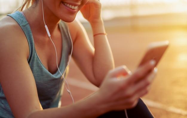 Gros plan d'une fille apte à écouter de la musique sur son téléphone.