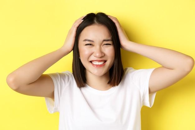 Gros plan d'une fille asiatique heureuse toucher ses cheveux et souriant, debout en t-shirt blanc sur jaune.