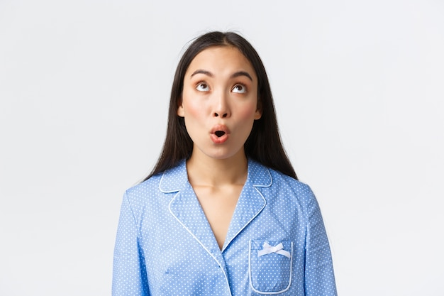 Gros plan d'une fille asiatique kawaii étonnée et impressionnée en pyjama bleu réagissant à des nouvelles incroyables, regardant avec émerveillement et dire wow, debout stupéfaite sur fond blanc.