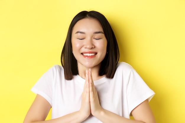 Gros plan d'une fille asiatique pleine d'espoir en t-shirt blanc, main dans la main en priant, geste namste et souriant, faisant un souhait ou plaidant, debout sur le jaune