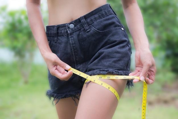 Gros plan fille bien faite avec un ruban à mesurer sur la jambe