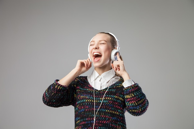 Gros plan de fille avec un casque chantant avec sa bouche grande ouverte sur fond gris