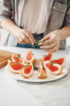 Gros plan de fille décoration plaque avec pamplemousse en tranches et romarin. concept de nutrition de remise en forme. copiez l'espace.