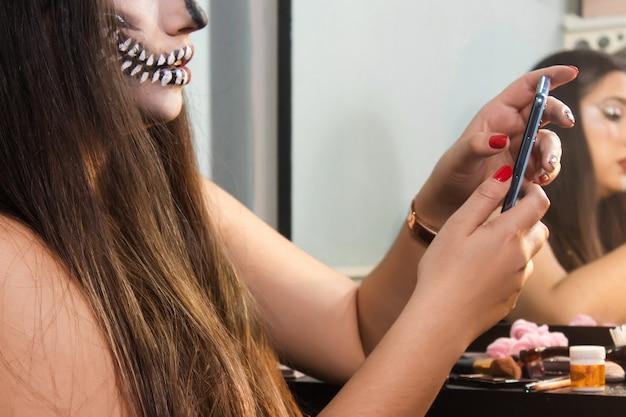 Gros plan d'une fille avec du maquillage de crâne d'halloween à l'aide de son téléphone intelligent dans sa chambre