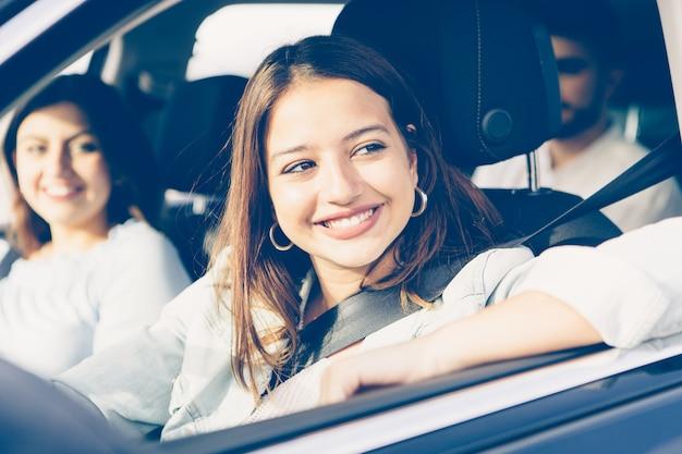 Gros plan d'une fille heureuse conduit une voiture avec ses amis