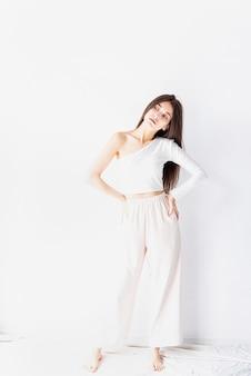 Gros plan d'une fille heureuse en pyjama blanc debout près du mur à la maison en souriant