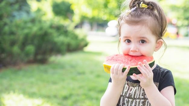 Gros plan, fille, manger, pastèque, parc