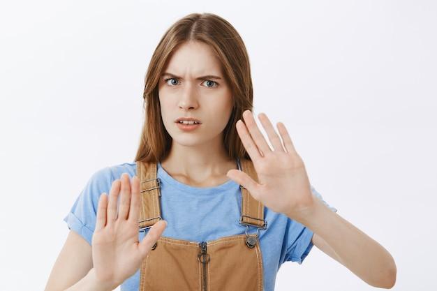 Gros plan d'une fille mécontente frustrée montrant le geste d'arrêt, interdire l'action, refuser