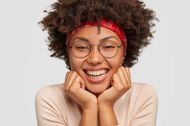 Gros plan d'une fille à la peau sombre touche les joues, se sent heureuse, apprécie une musique agréable et une bonne journée, porte de grandes lunettes rondes, des modèles sur un mur blanc. femme féminine sensuelle sourit largement
