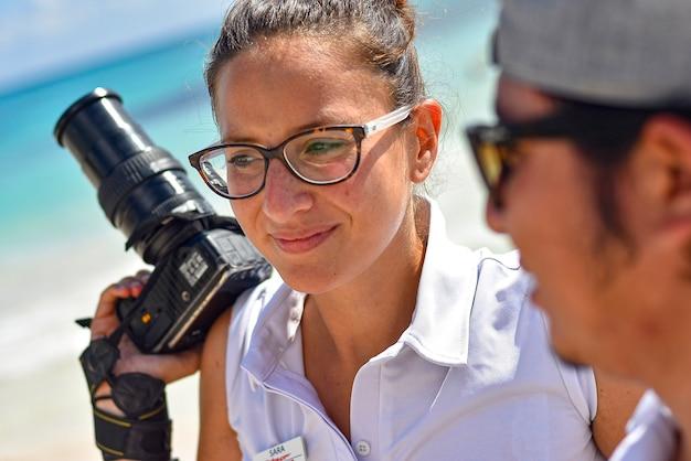 Gros plan d'une fille photographe avec un reflex à la main