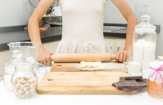 Gros plan d'une fille qui roule la pâte avec une broche en bois dans la cuisine