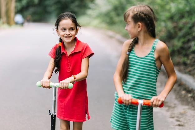 Gros plan, fille, regarder, son, ami, alors, équitation, scooters, sur, route