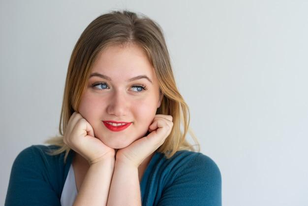Gros plan d'une fille rêveuse souriante aux lèvres rouges