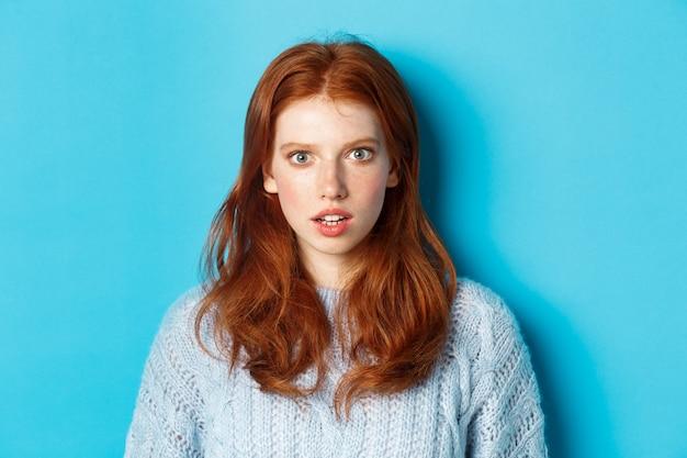 Gros plan d'une fille rousse étonnée regardant la caméra avec une incrédulité totale, debout choquée sur fond bleu
