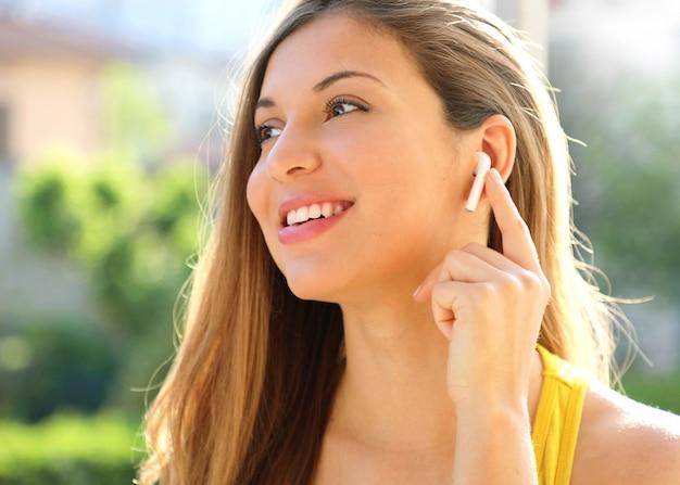 Gros plan d'une fille souriante sportive connectant des écouteurs sans fil à l'extérieur