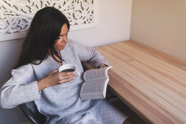 Gros plan, fille, tasse café, séance, chaise, livre lecture