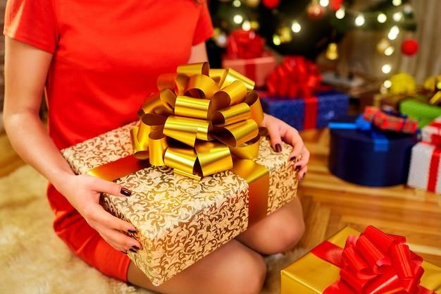 Gros plan, fille, tenant, elle, mains, grand, boîte, grand, arc doré, cadeau