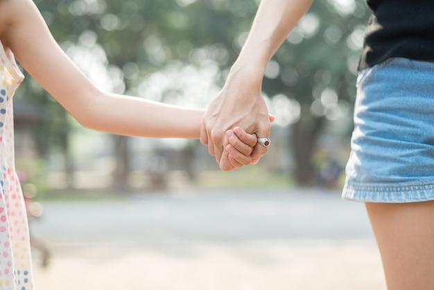 Gros plan fille tenant avec sa mère, se sentir réconforté et affectueux, heureux temps en famille