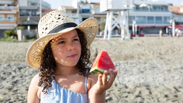 Gros plan fille tenant une tranche de pastèque