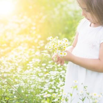 Gros plan, fille, tenue, blanc, fleurs, main