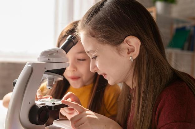 Gros plan des filles avec microscope