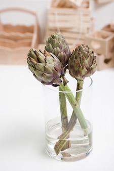 Gros plan d'une fleur d'artichaut dans un vase en verre sur fond de tableau blanc et de boîtes en bois. atelier de fleuriste, composition florale pour cadeaux, concept d'intérieur et de décoration