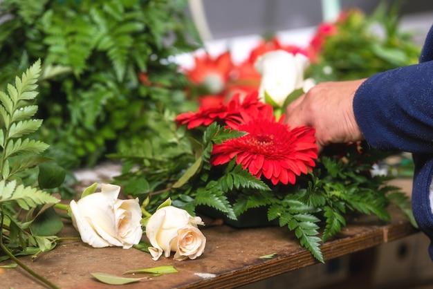 Gros plan de fleuriste femme créant un bouquet de fleurs.