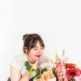 Gros plan, de, a, fleuriste femme, sentir, fleurs, sur, fond blanc