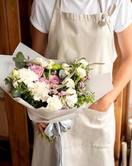 Gros plan fleuriste tenant le bouquet